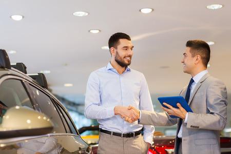 자동 비즈니스, 자동차 판매, 기술, 제스처 및 사람들이 개념 - 행복 한 남자와 자동차 딜러 자동차 쇼 또는 살롱에 악수하는 태블릿 pc 컴퓨터와 함께 스톡 콘텐츠