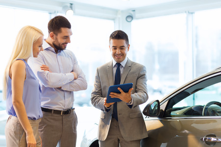 sale: auto business, car sale, technology and people concept - happy couple with car dealer in auto show or salon