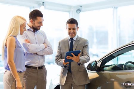autozaken, auto verkoop, technologie en mensen concept - gelukkig paar met autohandelaar in autoshow of salon Stockfoto