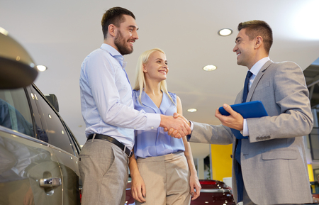shaking hands: auto business, car sale, technology, gesture and people concept - happy couple with car dealer shaking hands in auto show or salon