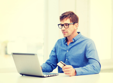 business, online banking, internet shopping concept - smiling man with laptop and credit card at home photo