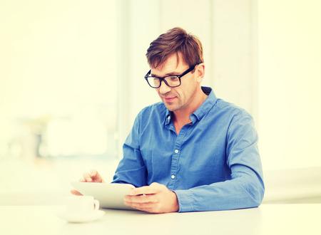 technologie et mode de vie, la distance notion d'apprentissage - bel homme travaillant avec Tablet PC et une tasse de café à la maison