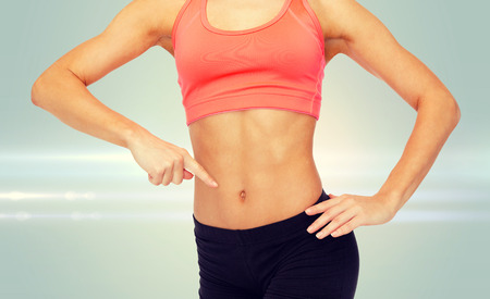 6 pack: fitness, exercise and diet concept - close up of woman pointing finger at her six pack Stock Photo