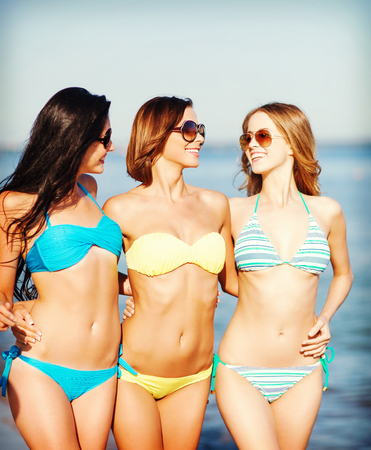 chilling out: summer holidays and vacation concept - girls in bikinis walking on the beach Stock Photo
