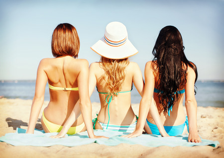 from side: summer holidays and vacation - girls sunbathing on the beach Stock Photo