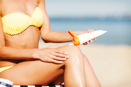 uv: summer holidays and vacation - girl putting sun protection cream on the beach chair