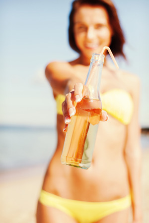 non alcoholic beer: summer holidays, vacation and beach concept - girl with bottle of drink on the beach