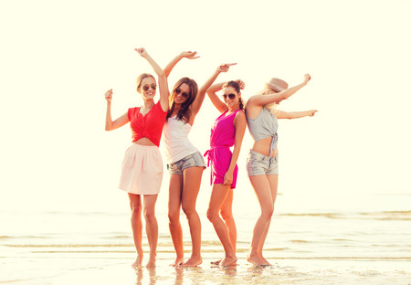 beach clothes: summer vacation, holidays, travel and people concept - group of smiling young women in sunglasses and casual clothes dancing on beach
