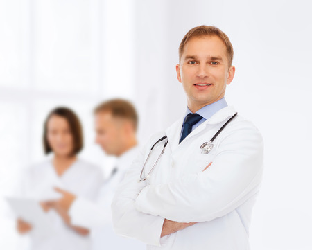 healthcare professional: healthcare, profession, teamwork, people and medicine concept - smiling male doctor with stethoscope in white coat over over group of medics