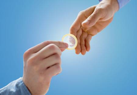 educacion sexual: personas, homosexualidad, sexo seguro, de educación sexual y de concepto de caridad - Cerca de feliz varones homosexuales par manos dando condón sobre fondo azul