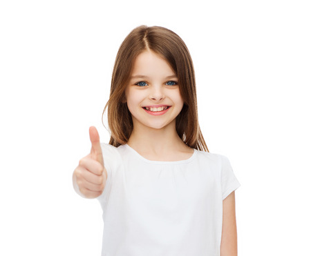 pre approval: t-shirt design and happy people concept - smiling little girl in blank white t-shirt showing thumbs up
