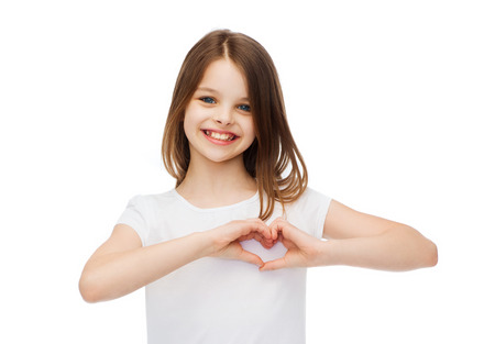 pre teen girl: friendship, t-shirt design and happy people concept - smiling little girl in white blank t-shirts showing heart with hands