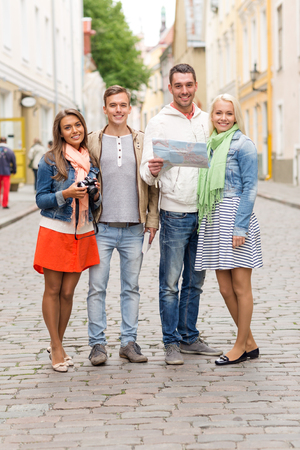 photocamera: travel, vacation, technology and friendship concept - group of smiling friends with map and photocamera exploring city
