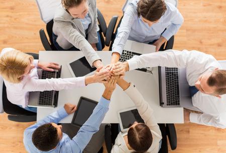 affaires, les gens, la technologie, la coopération et le travail d'équipe concept - Gros plan de l'équipe créative avec les ordinateurs portables et ordinateurs tablettes pc assis à table et se tenant les mains sur le dessus de l'autre dans le bureau