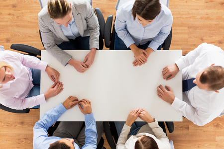 tops: business, people and team work concept - close up of creative team sitting at table in office