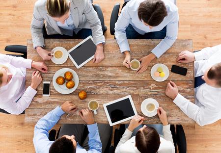 lunch: negocios, personas, descanso y trabajo en equipo concepto - cerca de la reuni�n del equipo creativo y de tomar caf� con magdalenas durante el almuerzo en la oficina Foto de archivo