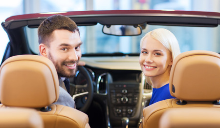 auto business, car sale, consumerism and people concept - happy couple sitting in car at auto show or salon photo