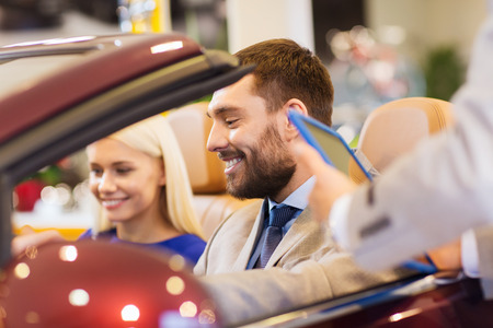 auto business, car sale, consumerism and people concept - happy couple with car dealer in auto show or salon photo