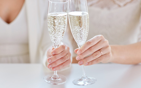nude lesbian: people, homosexuality, same-sex marriage, celebration and love concept - close up of happy married lesbian couple hands holding and clinking champagne glasses