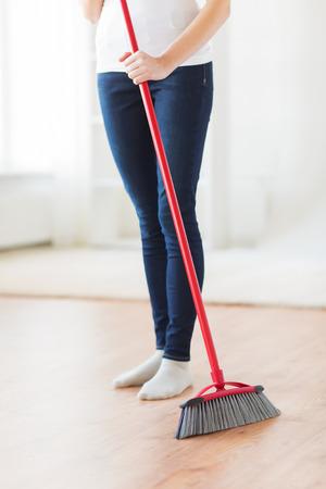 orden y limpieza: las personas, el trabajo dom�stico, la limpieza y el servicio de limpieza concepto - cerca de piernas de la mujer con la escoba Suelo arrebatador en casa