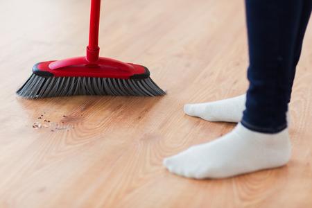 servicio domestico: las personas, el trabajo dom�stico, la limpieza y el servicio de limpieza concepto - cerca de piernas de la mujer con la escoba Suelo arrebatador en casa
