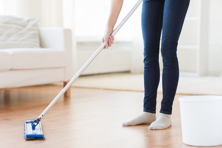 people, housework and housekeeping concept - close up of woman legs with mop cleaning floor at home Stock Photo