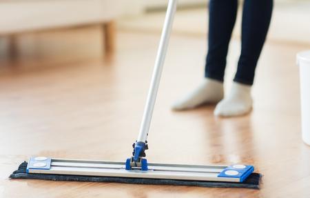 orden y limpieza: las personas, el trabajo dom�stico y de limpieza concepto - cerca de piernas de la mujer con piso de limpieza fregona en casa
