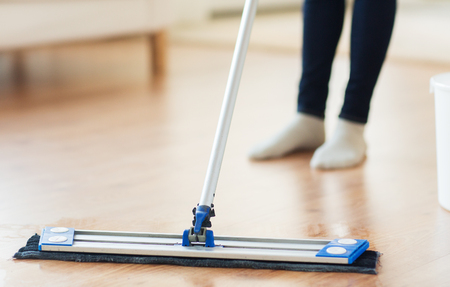 housekeeping: people, housework and housekeeping concept - close up of woman legs with mop cleaning floor at home Stock Photo