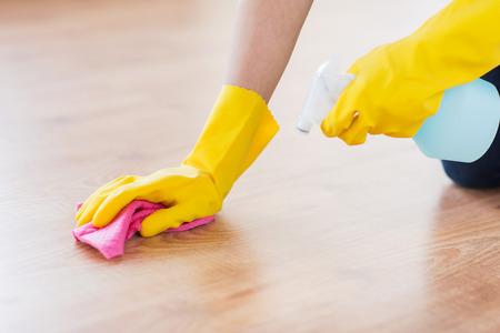 orden y limpieza: las personas, el trabajo doméstico y de limpieza concepto - cerca de la mujer en Glover goma con tela y aerosol detergente piso de la limpieza en el hogar