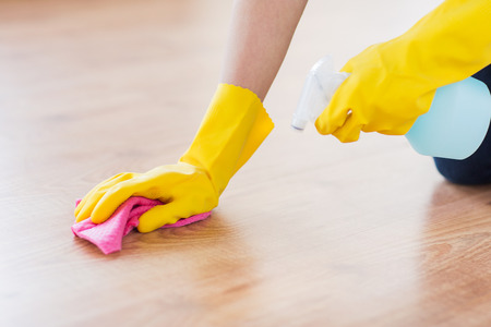 floor cloth: people, housework and housekeeping concept - close up of woman in rubber glover with cloth and detergent spray cleaning floor at home