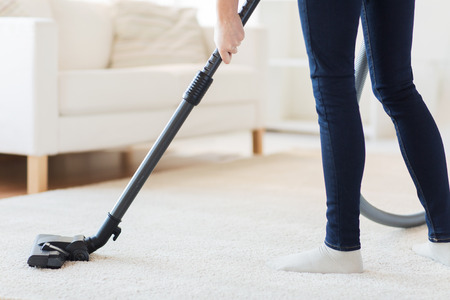 domestic chore: people, housework and housekeeping concept - close up of woman with legs vacuum cleaner cleaning carpet at home Stock Photo