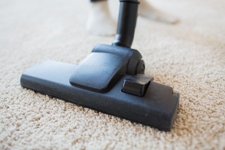 clean carpet: people, housework and housekeeping concept - close up of vacuum cleaner nozzle cleaning carpet at home Stock Photo