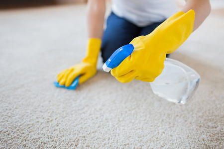 cleaning service: people, housework and housekeeping concept - close up of woman in rubber gloves with cloth and detergent spray cleaning carpet at home