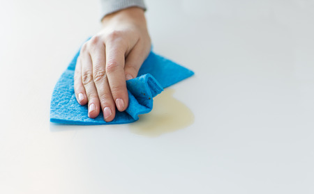 maid cleaning: people, housework and housekeeping concept - close up of woman hand cleaning spot from table surface with cloth at home Stock Photo
