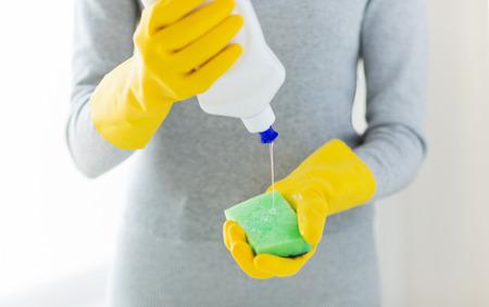 lavar platos: las personas, las tareas domésticas, lavar los platos y la limpieza concepto - cerca de la mujer de aplicar el jabón líquido de la botella limpiador a la esponja en casa
