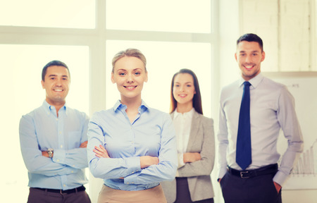 company job: business and office concept - smiling beautiful businesswoman with crossed hands and team in office