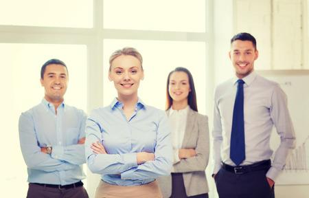 úspěšný: obchodní a kancelářské koncepce - usmívající se krásná obchodnice se zkříženýma rukama a tým v kanceláři