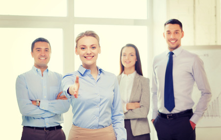 members: business and office concept - smiling beautiful businesswoman ready for handshake with team in office