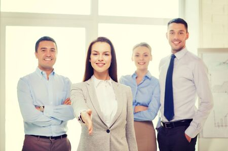 business and office concept - smiling beautiful businesswoman ready for handshake with team in office photo