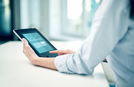 business, technology, statistics, progress and people concept - close up of woman with tablet pc computer showing growing charts at office or home photo