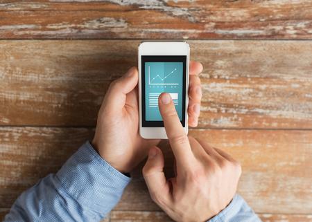 dedo: negocios, la educaci�n, las estad�sticas, las personas y la tecnolog�a concepto - cerca de las manos masculinas sosteniendo tel�fono inteligente y apuntando el dedo para graficar y texto en la pantalla en la mesa