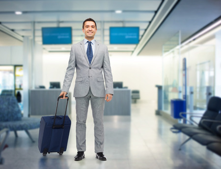 business trip, traveling, luggage and people concept - happy businessman in suit with travel bag over airport background Stockfoto
