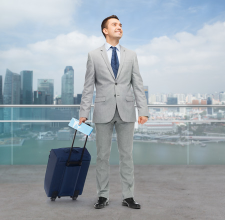 trip over: business trip, traveling, luggage and people concept - happy businessman in suit with travel bag and air ticket over city background Stock Photo