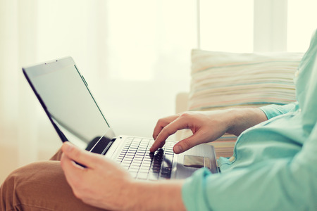 技術、ホームとライフ スタイル コンセプトをラップトップ コンピューターで作業と自宅のソファに座っている男のクローズ アップ