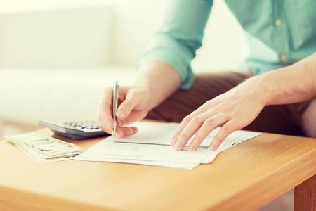 Ahorros, las finanzas, la economía y el hogar concepto - cerca del hombre con la calculadora contar dinero y haciendo notas en casa Foto de archivo - 38879361