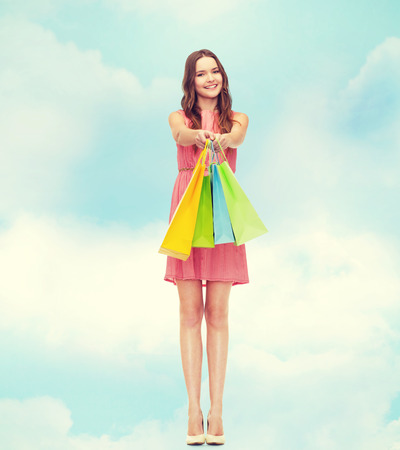 spending full: retail and sale concept - smiling woman in dress and high heels with many shopping bags Stock Photo