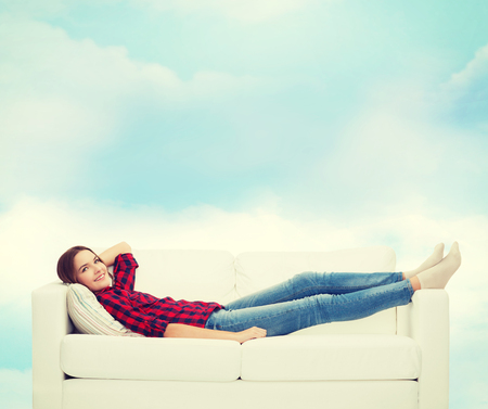 blue sky thinking: home, leisure and happiness concept - smiling teenage girl lying on sofa