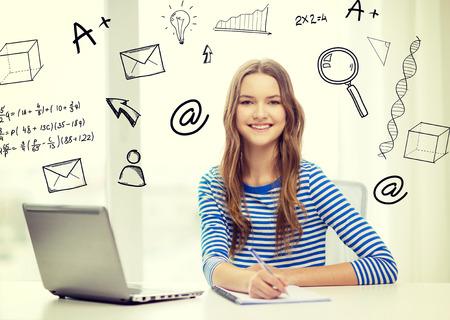 education: l'éducation, la technologie et le concept de la maison - sourire adolescente avec un ordinateur portable, carnet et un stylo à la maison