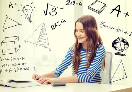 la educación, la tecnología y el concepto de hogar - sonriente niña estudiante con el libro, cuaderno y calculadora