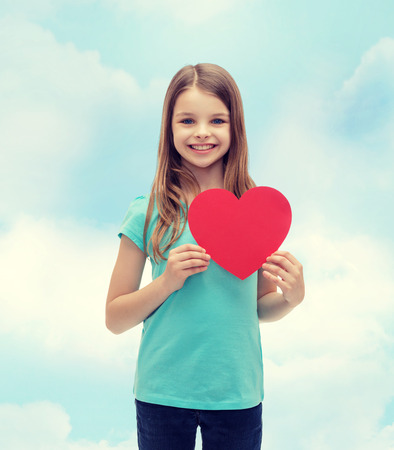 love, happiness and people concept - smiling little girl with red heart photo